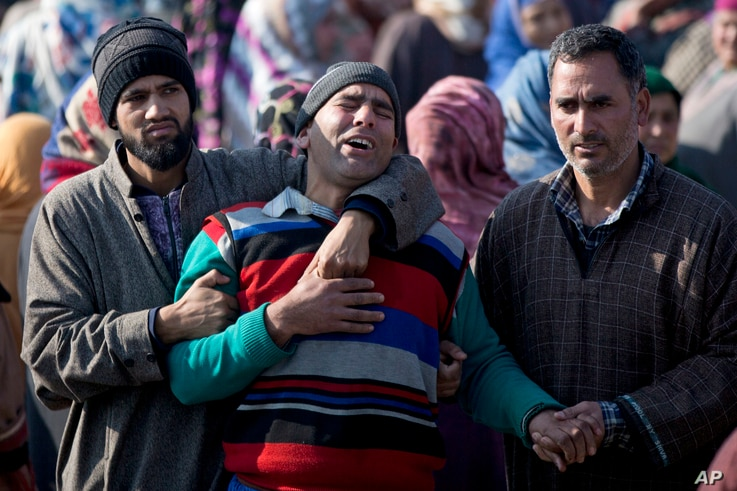 Kashmiri villagers comfort the grieving father of Murtaza, a 14-year-old civilian, during his funeral procession in Pulwama, south of Srinagar, Indian controlled Kashmir, Dec. 15, 2018. At least seven civilians were killed and nearly two dozens injur...