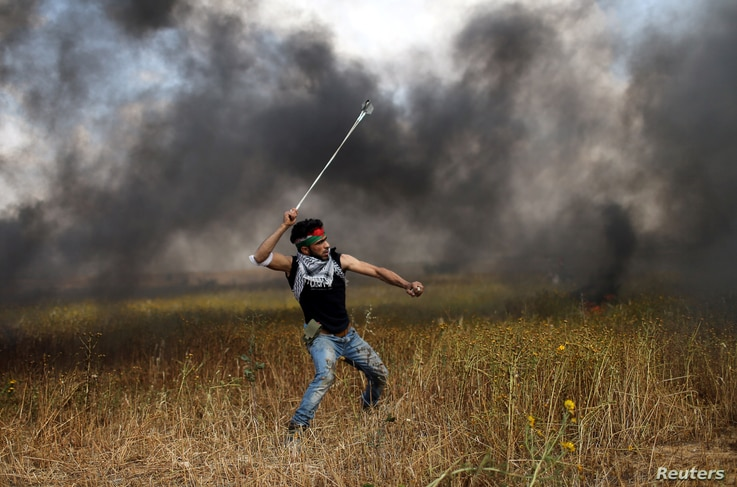 A Palestinian hurls stones at Israeli troops during a tent city protest along the Israel border with Gaza, March 30, 2018.