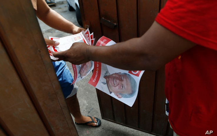 FILE - A man hands out campaign literature for Andres Manuel Lopez Obrador, in Acapulco, Mexico, June 19, 2018. The modern-day militarized drug fight, Lopez Obrador argued,has failed to stop narcotics smuggling and violence, and doesnot address t...