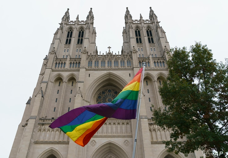 """A gay pride flag flies outside the Washington National Cathedral in Washington, Oct. 26, 2018, following a """"Thanksgiving and Remembrance of Matthew Shepard"""" service."""