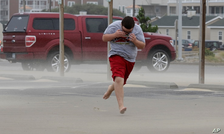 Eli White covers his face from the blowing sand in Nags Head, N.C., as the tail of Tropical Storm Hermine passes the Outer Banks, Sept. 3, 2016.