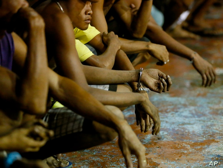 "FILE - Rounded up residents, mostly males, wait to be transported to a police station in the continuing operation of President Rodrigo Duterte's so-called ""War on Drugs"" campaign, at the slum community of Tondo, in Manila, Philippines, Sept. 30, 2016..."