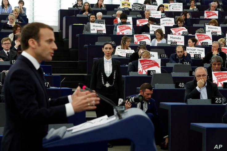 "European lawmakers raise placards reading ""Stop the War in Syria"" in protest against airstrikes launched by the U.S., Britain and France in Syria last week, as French President Emmanuel Macron delivers his speech at the European Parliament in Strasbo..."