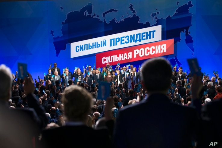 Supporters of incumbent Vladimir Putin vote to officially nominate him for presidency in Moscow, Russia, Tuesday, Dec. 26, 2017. Putin is set to easily win a fourth term in office in the March 18 election, with his approval ratings topping 80 percent...