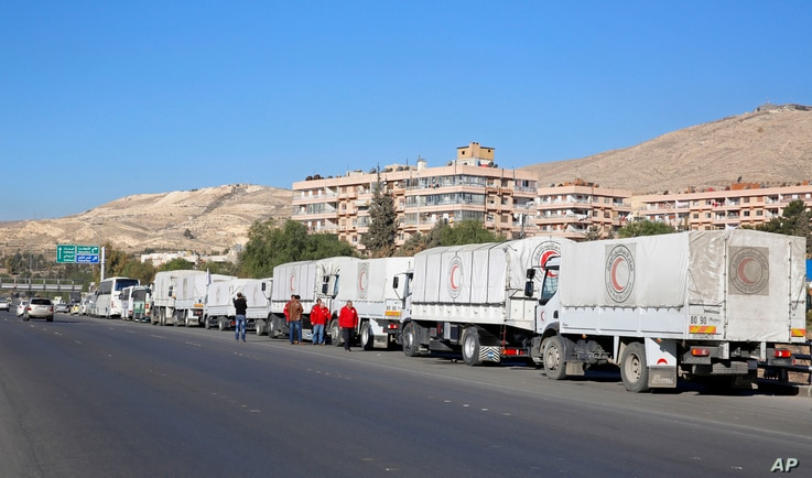 A convoy of humanitarian aid waits in front of the United Nations Relief and Works Agency (UNRWA) offices before making their way into the government besieged rebel-held towns of Madaya, al-Zabadani and al-Moadhamiya in the Damascus countryside, as p...