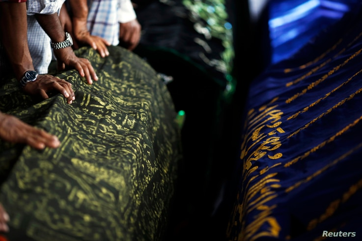 People prepare to pray around the coffins of victims of a fire during their funeral at Yaeway cemetery, Rangoon, Burma, April 2, 2013.