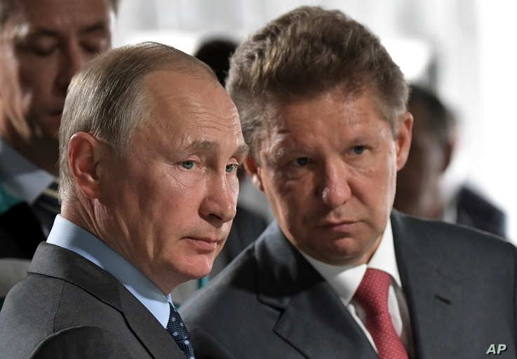 FILE - Russian President Vladimir Putin, left, and Alexei Miller, Russian natural gas giant Gazprom CEO, attend a meeting of major investment projects implementation in the Russian Far East as part of his trip to the Nizhne-Bureiskaya Hydroelectric P...
