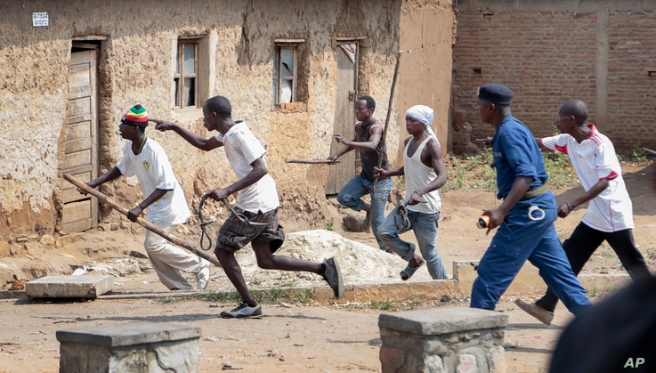 Members of the Imbonerakure pro-government youth militia chase after opposition protesters, unhindered by police, in the Kinama district of the capital Bujumbura, Burundi, May 25, 2015.