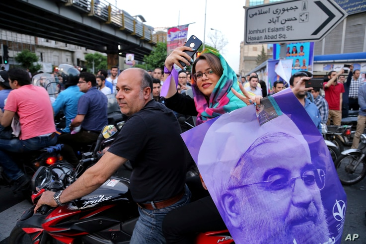 A supporter of Iran's President Hassan Rouhani, who is running for a second term in office, holds his poster during a campaign rally in downtown Tehran, May 16, 2017.