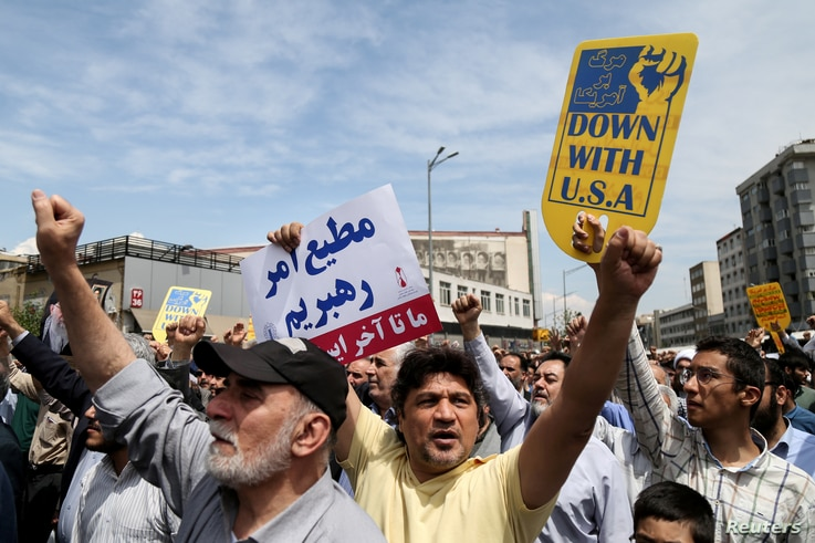 FILE PHOTO: Iranians shout slogans during a protest against President Donald Trump's decision to walk out of a 2015 nuclear deal, in Tehran, Iran, May 11, 2018.
