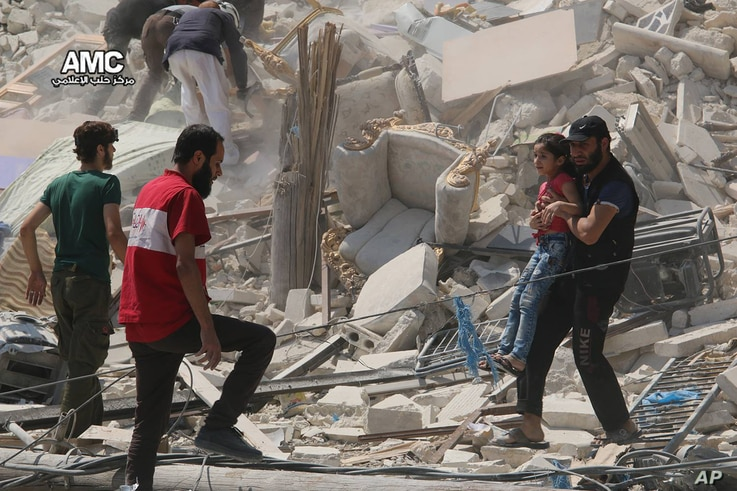 FILE - This photo provided by the Syrian anti-government activist group Aleppo Media Center (AMC), shows a Syrian man carrying a girl away from the rubble of a destroyed building after barrel bombs were dropped on the Bab al-Nairab neighborhood in Al...