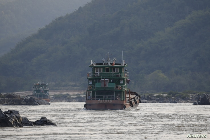 FILE - Chinese cargo ships sail on the Mekong river near the Golden Triangle at the border between Laos, Myanmar and Thailand March 1, 2016.