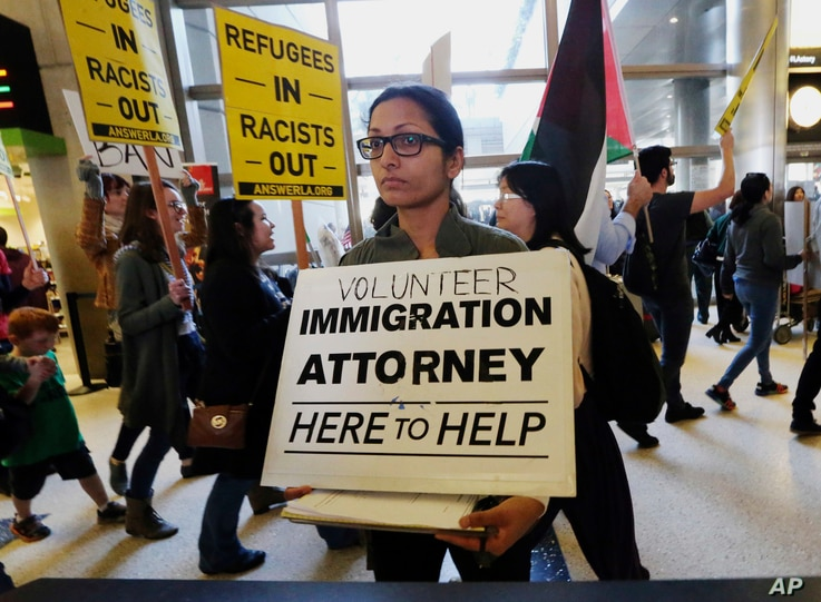 A woman offers legal services at the customs arrival area as demonstrators opposed to President Donald Trump's executive orders barring entry to the U.S. by Muslims from certain countries march behind at the Tom Bradley International Terminal at Los ...