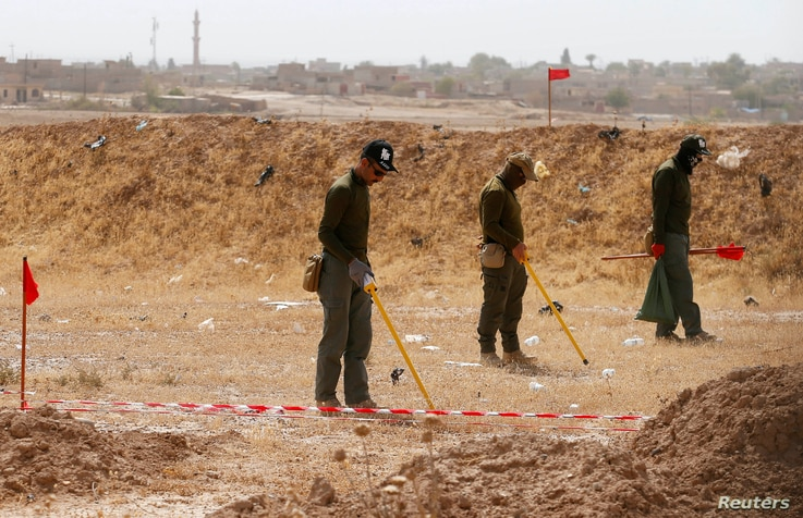 FILE - Mine clearers search for mines and explosive devices at Hammam al-Alil city south of Mosul, Iraq, July 29, 2017.