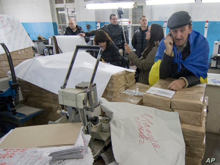 Members of regional election commission inspect voters ballots in a printing house in Mariupol, a major port and steel city in Ukraine's east, Oct. 25, 2015.