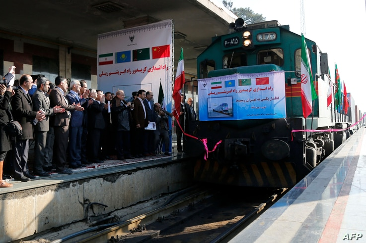 FILE - Iranian officials applaud on the platform as the first train connecting China and Iran arrives at Tehran Railway Station on Feb. 15, 2016.