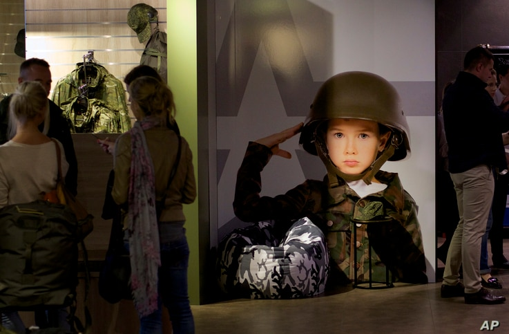 FILE - Customers visit the Russian Army store in downtown Moscow, Russia, July 21, 2015. The Russian Army Store opened earlier this year as an upmarket venue selling a wide range of patriotic goods - from mugs with Putin's portrait to limited-editi...