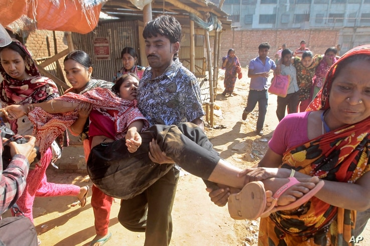 Garment workers assist injured colleagues during a clash with police in Ashulia on the outskirts of Dhaka, Bangladesh, Nov. 12, 2013.