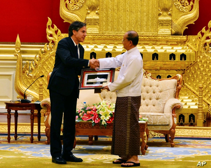 Myanmar President Thein Sein, right, shakes hands with U.S. Deputy Secretary of State Antony Blinken, left, as he presents gift during their meeting at Presidential Palace, May 21, 2015, in Naypyitaw, Myanmar. (