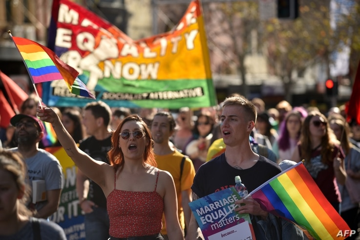 Supporters of same-sex marriage carry banners and shout slogans as they march in Sydney, Australia, Aug. 6, 2017.