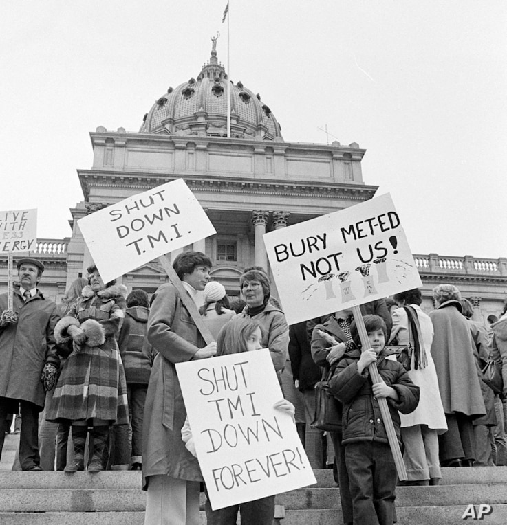 Two mothers along with their children carry signs in front of the State Capitol in Harrisburg, Penn., joining other anti-nuclear power plant demonstrators urging the shut-down of Three Mile Island (TMI) nuclear power plant near Harrisburg, April 8, 1...