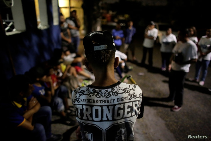 Young people listen to members of Raza Nueva in Christ, a project of the archdiocese of Monterrey, during a visit to a neighbourhood in the municipality of Juarez, on the outskirts of Monterrey, Mexico, May 30, 2016.