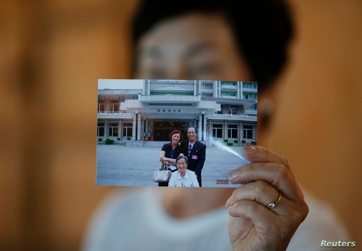 FILE - Kim Young-ja, a sister of Kim Young-nam who is a South Korean abductee living in North Korea, poses for photographs with a picture showing her abducted brother (R, in picture) taken during a reunion in 2006, July 2, 2014.