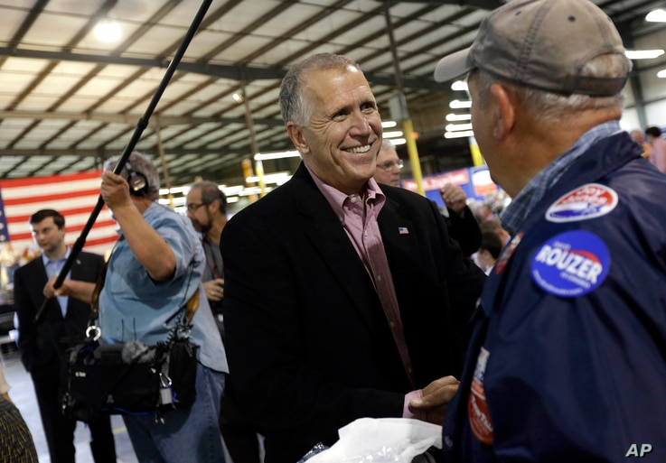 U.S. Senate candidate and Speaker of the N.C. House Thom Tillis speaks with a supporter during a conservative rally in Smithfield, N.C., Oct. 24, 2014.