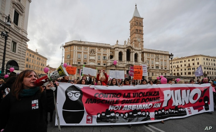 """Women hold a banner reading in Italian, """"Against the male violence on women we have a plan,"""" as they take part in a march marking the International Day for the Elimination of Violence against Women, in Rome, Nov. 25, 2017."""