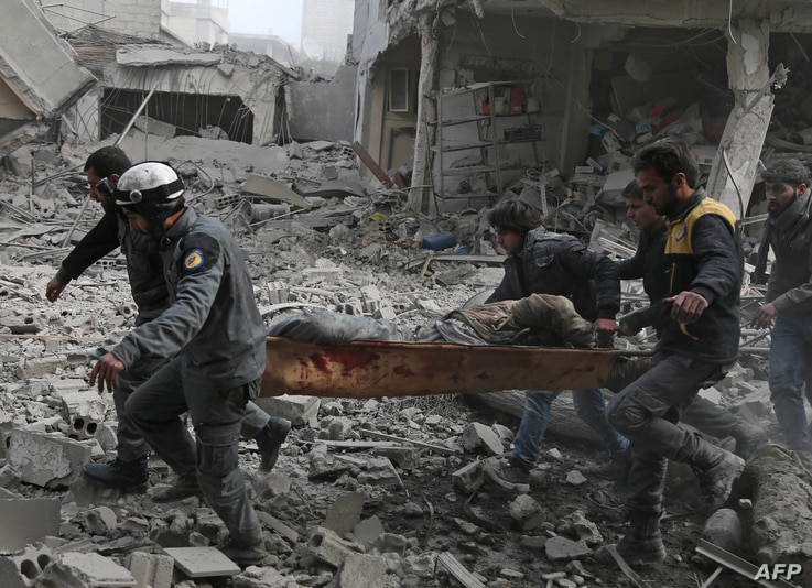 Graphic content / Members of the Syrian civil defence evacuate an injured civilian on a stretcher from an area hit by a reported regime air strike in the rebel-held town of Saqba, in the besieged Eastern Ghouta region on the outskirts of the capital ...
