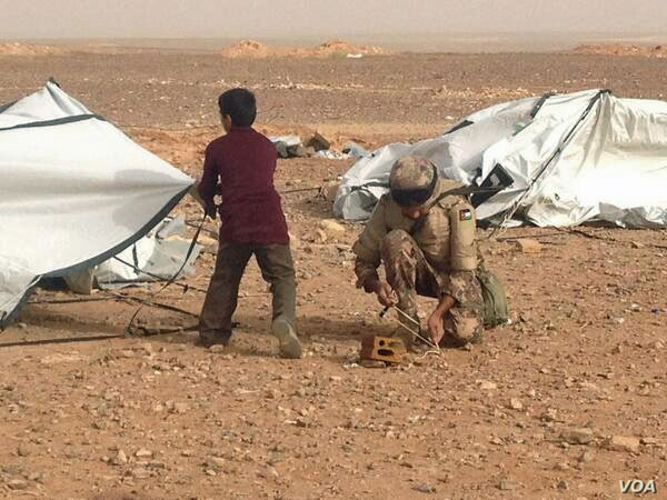"""A Jordanian soldier helping a young Syrian refugee put back up a tent blown down by the relentless wind. The UNHCR calls Jordan the """"model host."""""""