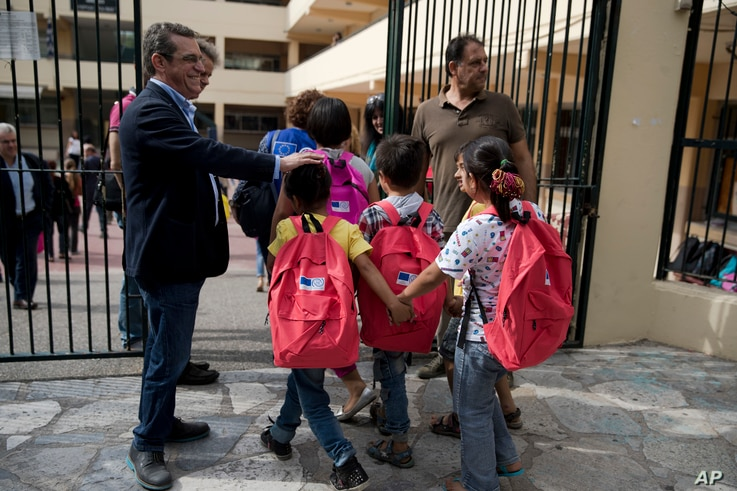 Refugee children enter a primary school in Athens on the first day of lessons under the new refugee schooling program on October 10, 2016. More than 60,000 refugees are stranded in Greece by European border closures.