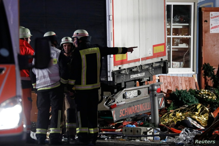 Firefighter stand beside a truck at a Christmas market in Berlin, Dec 19, 2016 after the truck ploughed into the crowded Christmas market in the German capital.