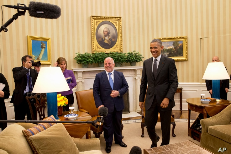 Iraqi Prime Minister Haider Al-Abadi and President Barack Obama get up from their seats after their meeting in the Oval Office of the White House in Washington, April 14, 2015.