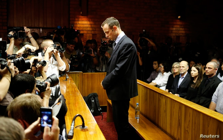 Oscar Pistorius stands at the dock before the start of proceedings at the Pretoria magistrates court, February 22, 2013.