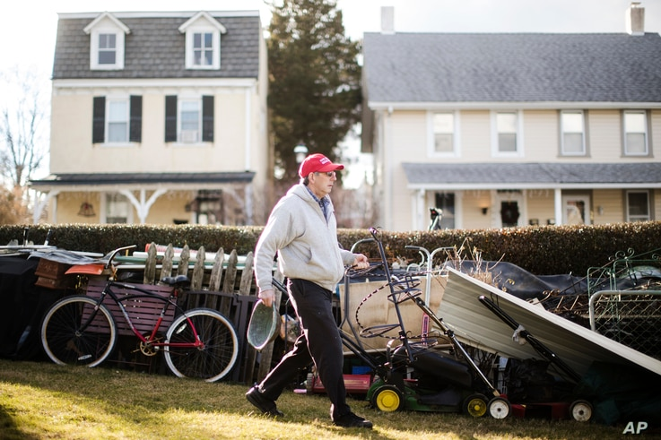 John Buckley, a Republican who relies on disability benefits and voted for Donald Trump, moves scrap metal at his home in Malvern, Pennsylvania.