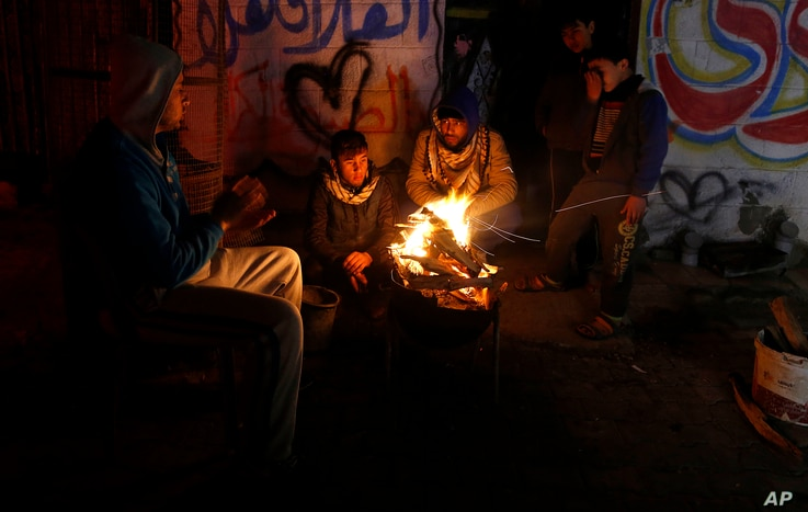 FILE -- In this Jan. 25, 2016 file photo, Palestinians, who get only several hours of electricity a day, sit around a fire outside their home in Gaza City. Israel said Thursday, April 27, 2017, that it was informed that the Palestinian self-rule gove...