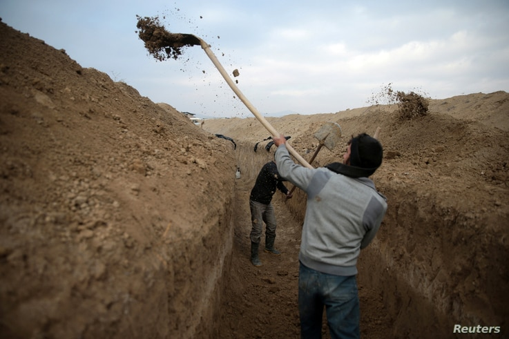 Rebel fighters dig a trench on the forth day of the truce, on al-Rayhan village front near the rebel held besieged city of Douma, in the eastern Damascus suburb of Ghouta, Syria Jan. 2, 2017.