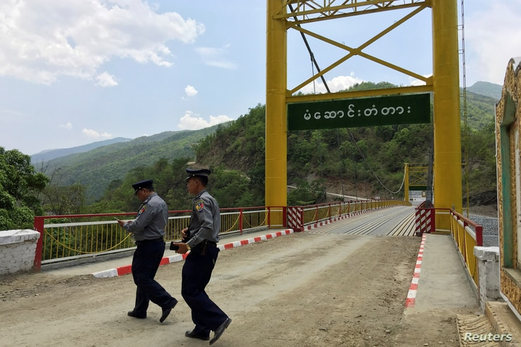 FILE - Police officers survey a bridge in Myanmar's Chin state, May 10, 2016, near the border with India where huge quantities of ingredients for the yaba drug are made.