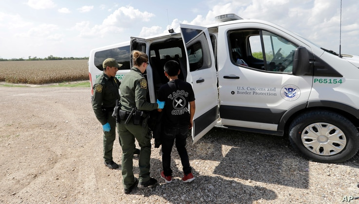 U.S. Border Patrol agents load migrant Gerberht Caraac, from Guatemala, into a van after he was caught trying to illegally enter the United States, Monday, June 25, 2018, in Hidalgo, Texas.