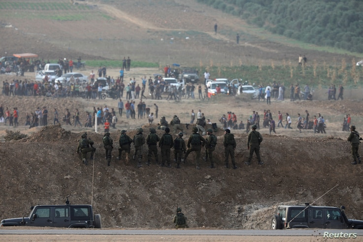 Israeli soldiers are seen next to the border fence on the Israeli side of the Israel-Gaza border as Palestinians protest on the Gaza side of the border, Israel, Oct. 19, 2018.