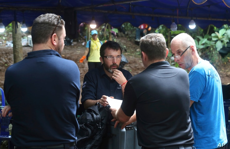 Australian Federal Police and Defense Force personnel talk each other near a cave where 12 boys and their soccer coach are trapped, in Mae Sai, Chiang Rai province, in northern Thailand, July 5, 2018.