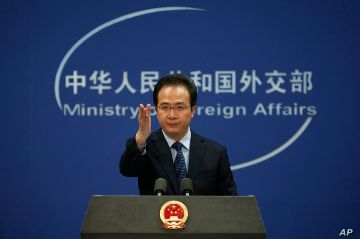 China's Foreign Ministry spokesman Hong Lei gestures during a daily briefing at the Ministry of Foreign Affairs office in Beijing, April 5, 2016.