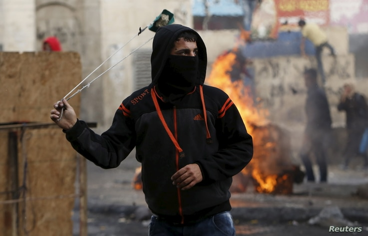 A Palestinian protester uses a sling to hurl stones at Israeli troops in Hebron, West Bank, Nov. 5, 2015. Israel's policies toward Palestinians will be discussed when U.S. President Barack Obama and Israeli Prime Minister Benjamin Netanyahu meet Mond...