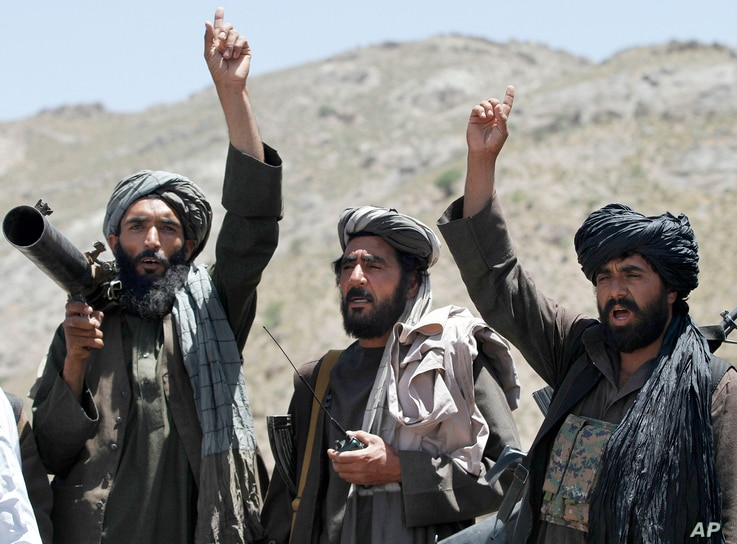 FILE - Taliban fighters react to a speech by their senior leader in the Shindand district of Herat province, Afghanistan.