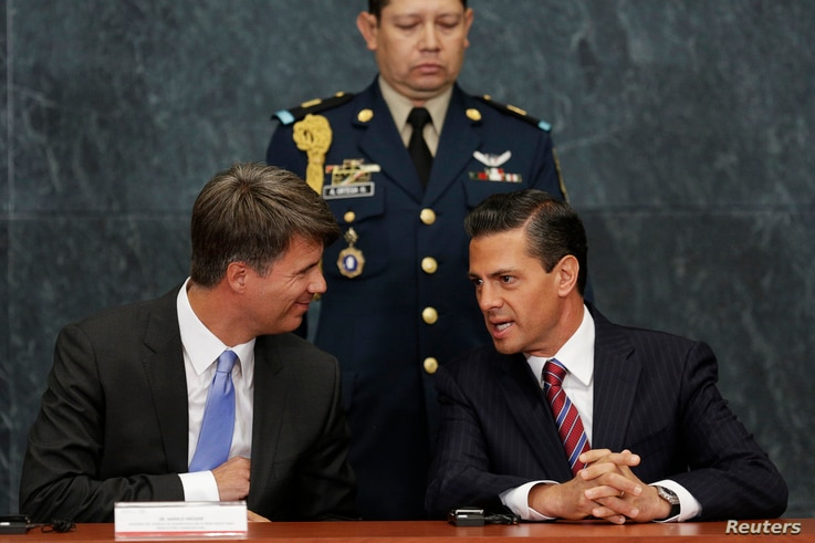 FILE - Mexico's President Enrique Pena Nieto (R) chats to BMW production chief Harald Krueger (L) during the announcement of the new BMW factory in Mexico, in Mexico City, July 3, 2014.