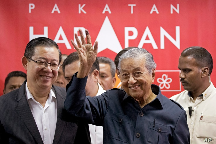 Malaysia's Prime Minister Mahathir Mohamad, center, waves next to newly appointed Finance Minister Lim Guan Eng, left, after a press conference to announce his cabinet members in Petaling Jaya, May 12, 2018.
