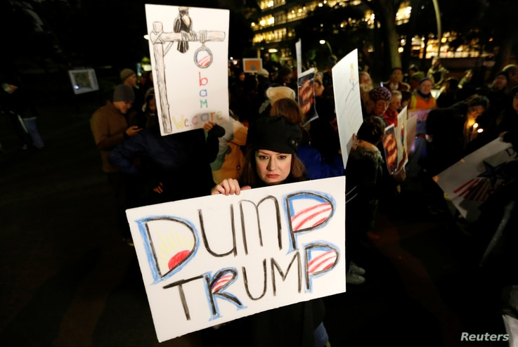 A woman holds an anti-U.S. President Donald Trump placard during a rally in Tokyo, Japan, Jan. 20, 2017.