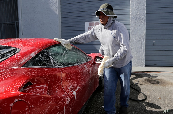 FILE - Jorge Tume washes a car in Miami, Florida, June 27, 2017.