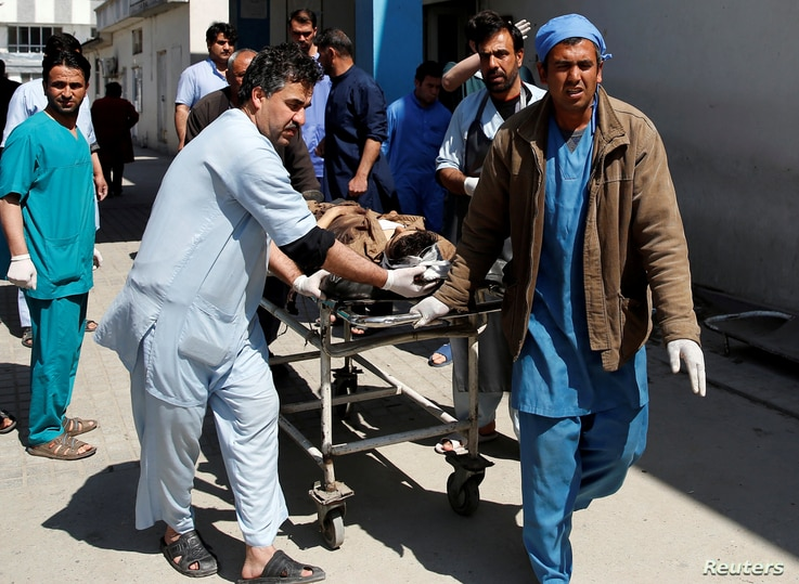 Men transport a victim to a hospital after a blast in Kabul, Afghanistan, March 21, 2018.